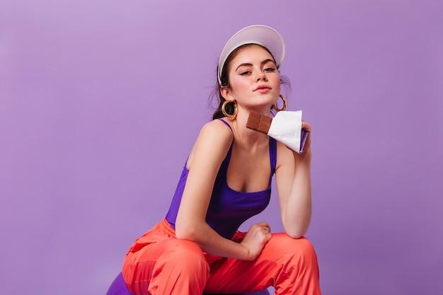 Mulher elegante com brincos enormes e boné olhando para a frente e segurando uma barra de chocolate na parede roxa