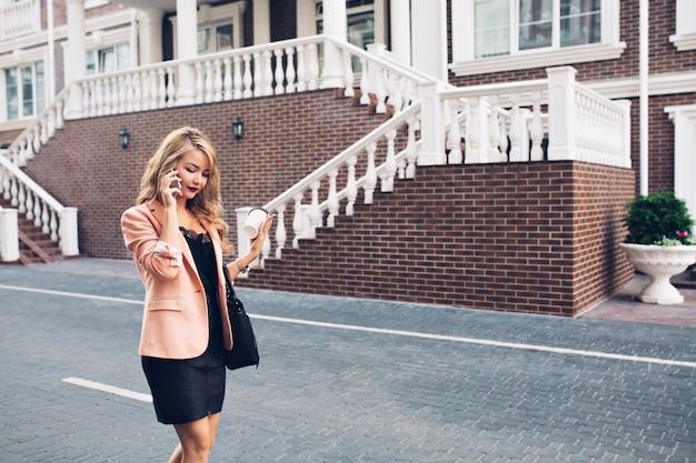 Mulher elegante com cabelo comprido, andando de vestido preto na rua em fundo de casa real. ela está falando ao telefone, olhando para baixo.