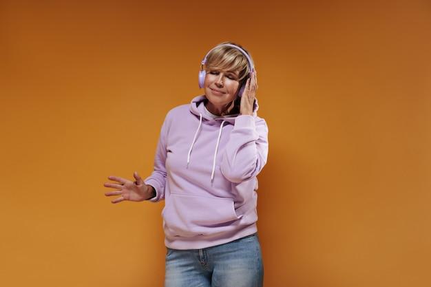 Mulher elegante com cabelo loiro curto, com capuz rosa moderno e jeans, ouvindo música e posando com fones de ouvido lilás.