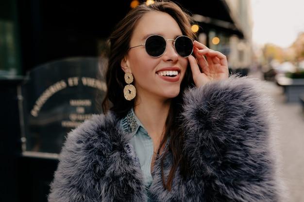 Mulher elegante com cabelos escuros posando divertidamente na rua.