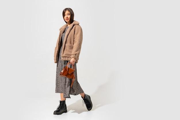 Mulher elegante com casaco de pele bege e vestido posando. comprimento total.