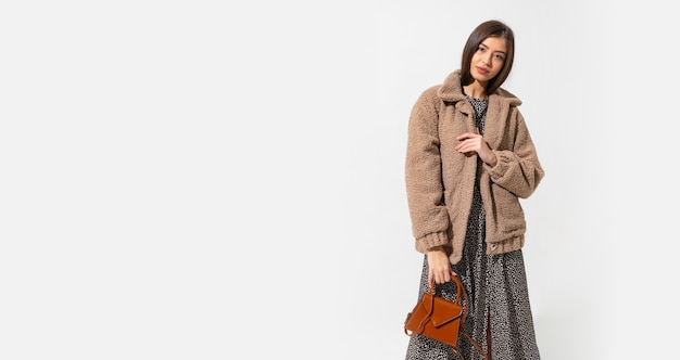 Mulher elegante com casaco de pele bege e vestido posando.