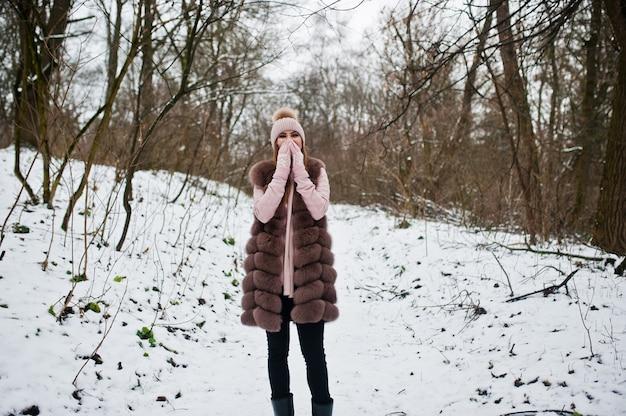 Mulher elegante com casaco de pele e chapelaria na floresta de inverno.