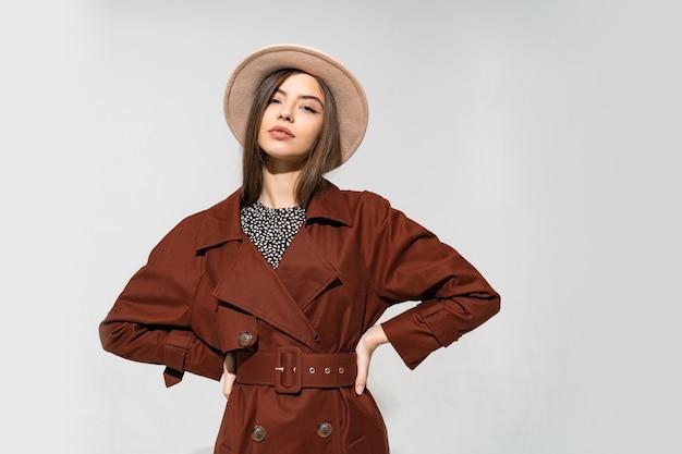 Mulher elegante com casaco marrom e chapéu bege posando