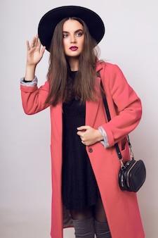 Mulher elegante com casaco rosa e chapéu preto posando