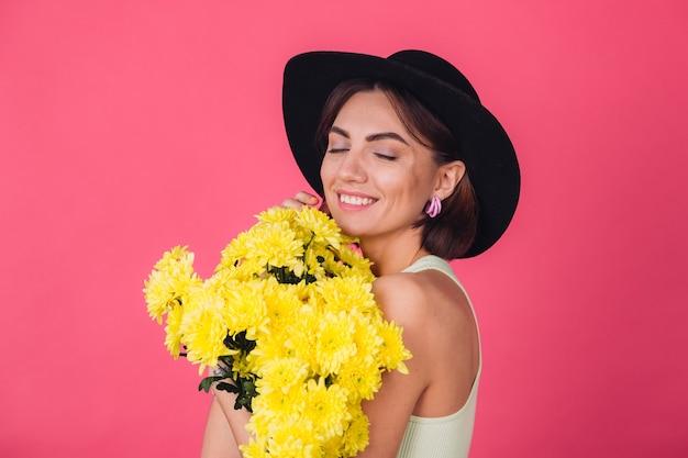 Mulher elegante com chapéu, abraçando um grande buquê de ásteres amarelos, clima de primavera, emoções felizes, espaço isolado, olhos fechados