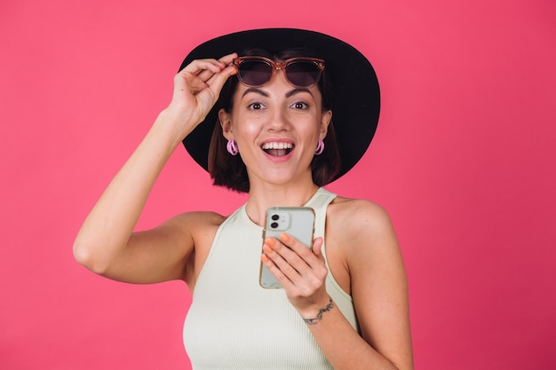 Mulher elegante com chapéu e óculos de sol na parede rosa vermelha