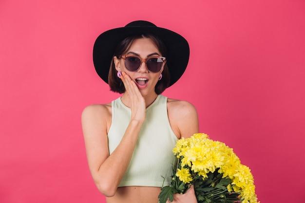 Mulher elegante com chapéu e óculos escuros, segurando um grande buquê de ásteres amarelos, clima de primavera, emoções emocionadas e espantadas, boca aberta espaço isolado