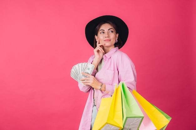Mulher elegante com chapéu na parede rosa vermelha