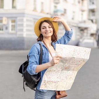Mulher elegante com chapéu segurando o mapa local