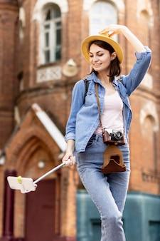 Mulher elegante com chapéu tomando uma selfie ao ar livre