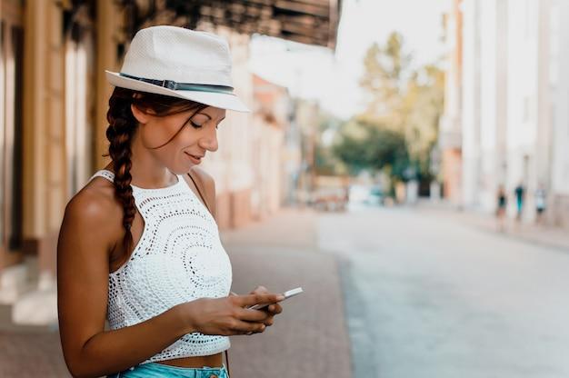 Mulher elegante com chapéu usando o telefone do lado de fora.