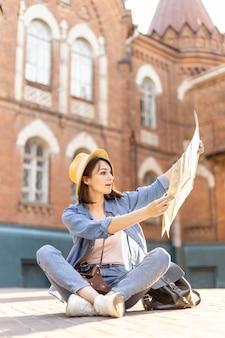 Mulher elegante com chapéu, verificando o mapa local
