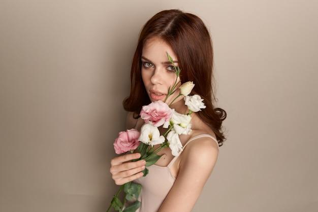 Mulher elegante com charme de flores e fundo bege luxuoso