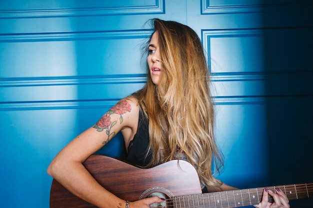 Mulher elegante com guitarra perto da parede azul