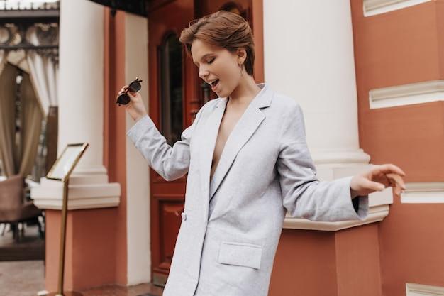 Mulher elegante com jaqueta grande, andando pela cidade. mulher atraente de cabelo curto e terno cinza sorrindo e curtindo o clima de primavera lá fora