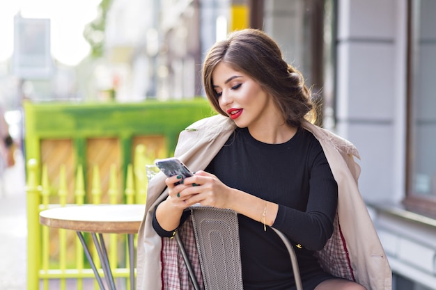Mulher elegante com lábios vermelhos usando um smartphone de rolagem de casaco bege enquanto está sentada em um refeitório ao ar livre