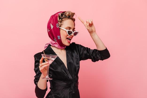 Mulher elegante com lenço de seda e óculos segurando uma taça de martini na parede rosa