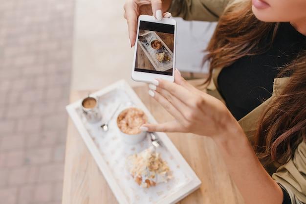 Mulher elegante com manicure branca segurando o smartphone enquanto desfruta do almoço