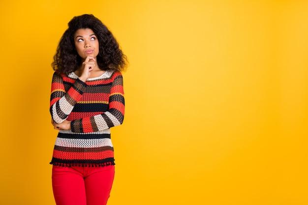 Mulher elegante com penteado afro posando contra a parede laranja