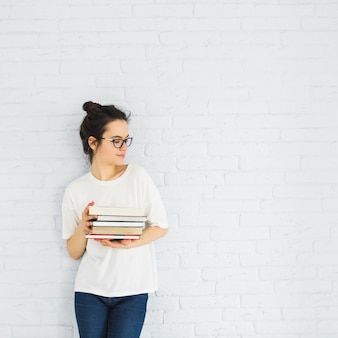 Mulher elegante com pilha de livros