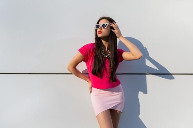 Mulher elegante com roupas de verão e óculos escuros posando sobre uma parede urbana branca.