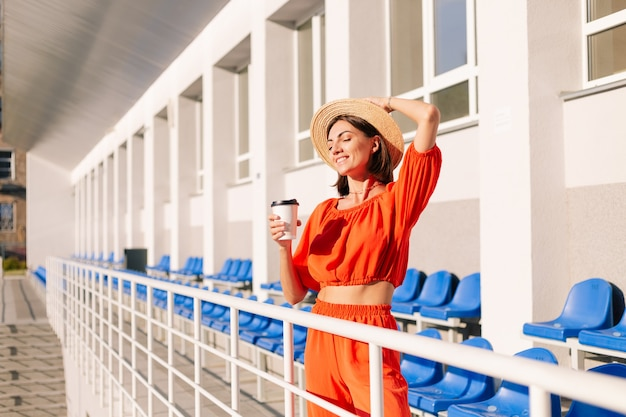 Mulher elegante com roupas laranja ao pôr do sol no estádio da ciclovia posando com uma xícara de café