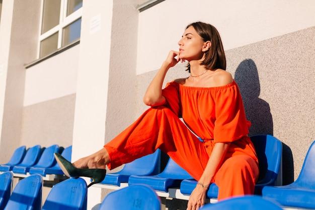 Mulher elegante com roupas laranja ao pôr do sol no estádio da ciclovia posando