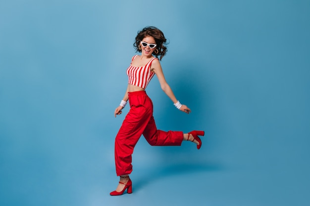 Mulher elegante com roupas no estilo dos anos 80 corre na parede azul
