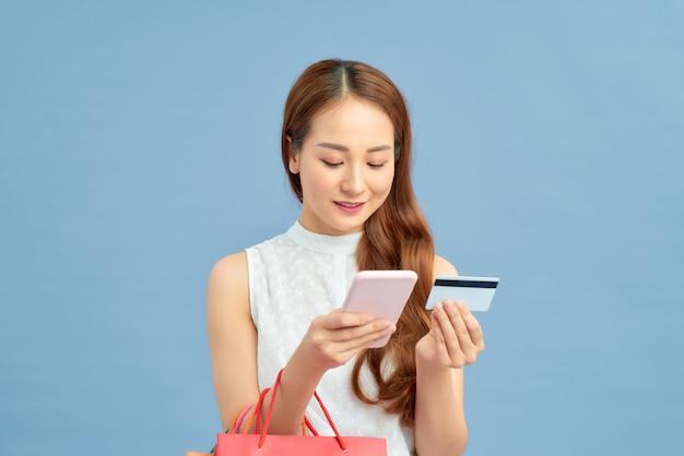 Mulher elegante com sacola de compras, cartão de crédito e telefone no fundo da parede azul