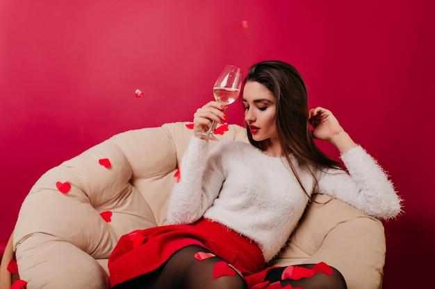 Mulher elegante com saia vermelha posando com confetes coloridos depois da festa