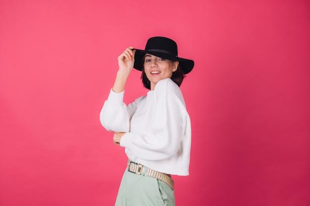 Mulher elegante com suéter branco casual e chapéu na parede rosa vermelha