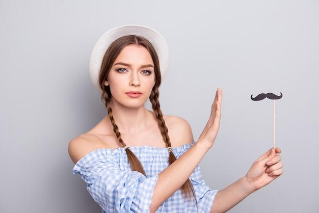 Mulher elegante com tranças e chapéu posando contra a parede branca