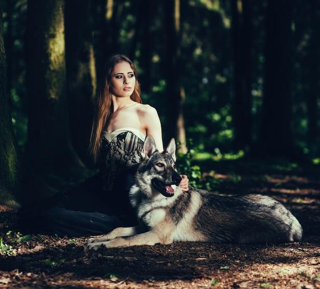 Mulher elegante com um cachorro na floresta