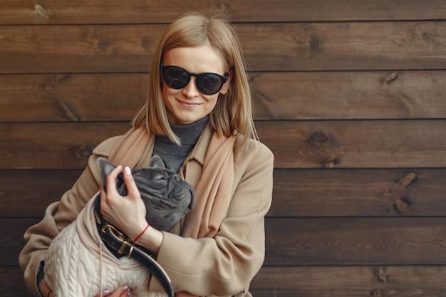 Mulher elegante com um casaco marrom com bulldog preto