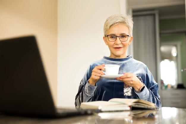 Mulher elegante com um corte de cabelo curto se senta em uma mesa com um laptop
