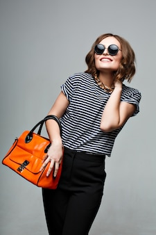 Mulher elegante com uma bolsa laranja e óculos de sol redondos grandes. vestida com roupa elegante, camisa listrada e calça preta.