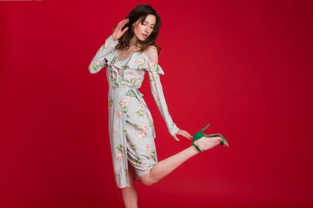 Mulher elegante com vestido de tendência da moda de verão posando em vermelho