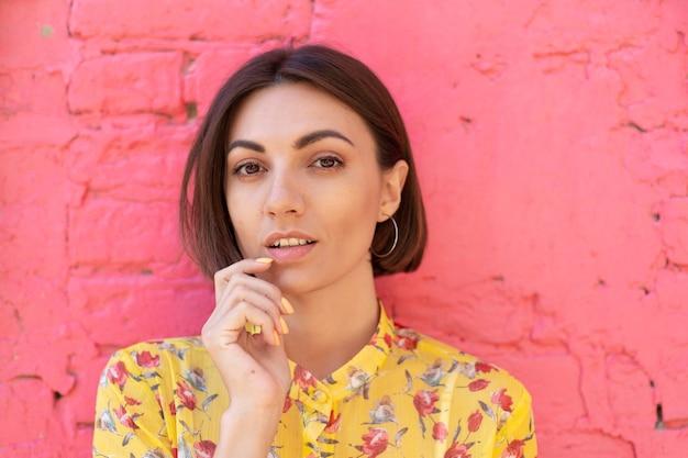 Mulher elegante com vestido de verão amarelo na parede de tijolo rosa feliz, calma e positiva