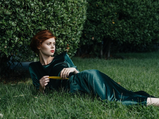 Mulher elegante com vestido verde encontra-se no gramado com o charme da viagem de ar fresco.