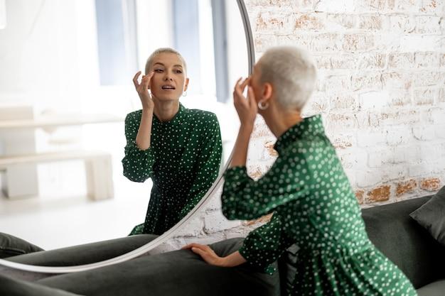 Mulher elegante com vestido verde olha seu rosto no espelho, preparando-se para sair. estilo feminino e conceito de beleza