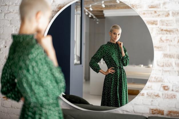 Mulher elegante com vestido verde se olha no espelho, preparando-se para sair. estilo feminino e conceito de beleza