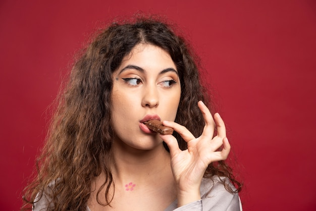 Mulher elegante comendo chocolate.