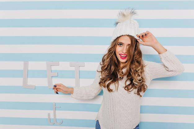 Mulher elegante de cabelos castanhos olhando e sorrindo com confiança. retrato de mulher com suéter de 24 anos em movimento contra uma parede listrada