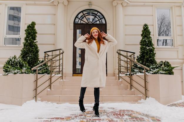 Mulher elegante de gengibre com casaco de inverno, posando em frente a uma bela casa. tiro ao ar livre da elegante garota ruiva.