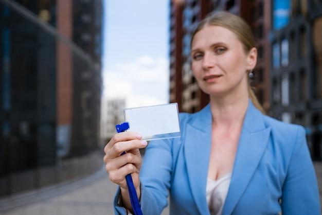Mulher elegante de negócios com um casaco azul com um distintivo na mão perto de um prédio comercial