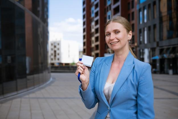Mulher elegante de negócios com um casaco azul e um distintivo na mão de um prédio de escritórios