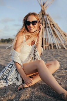 Mulher elegante de óculos escuros sentada na praia ao pôr do sol