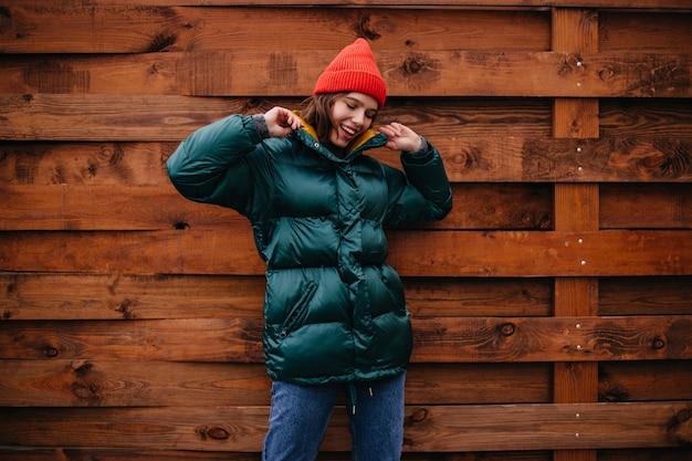 Mulher elegante de ótimo humor posando em parede de madeira