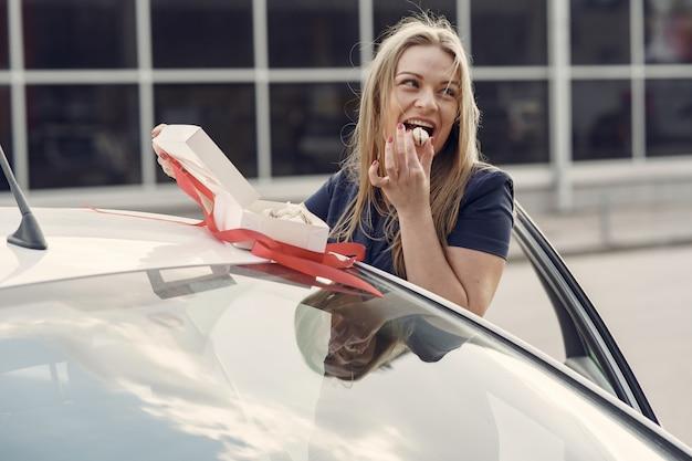 Mulher elegante, de pé ao lado do carro